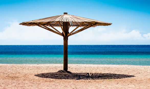 wooden beach umbrella on the shore without people of the Red Sea in Egypt during quarantine