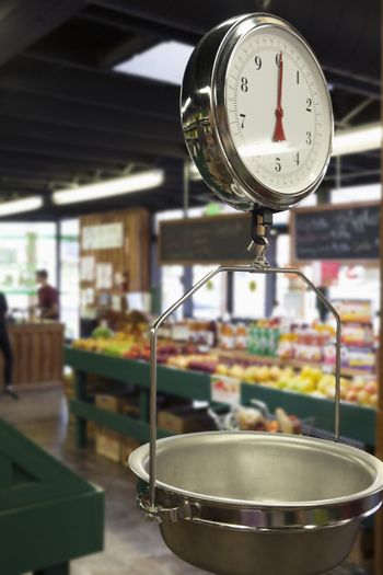Produce scale in supermarket with people in background