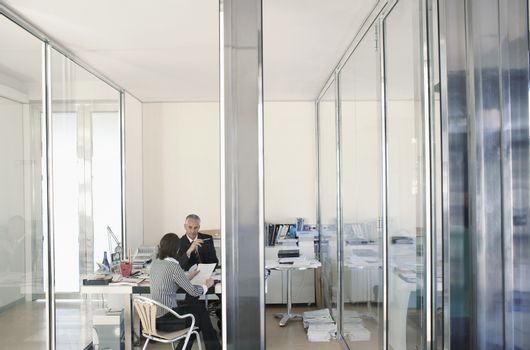 Two businesspeople sitting in office having meeting elevated view.