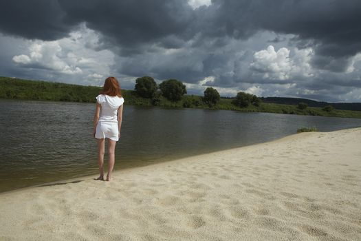Woman Standing by River under Storm Clouds