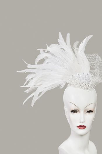 Feather fascinator on mannequin against gray background