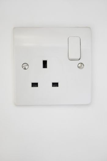 Electrical outlet attached on white wall