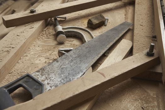 Carpenter's Saw and Clamp Among Wood Shavings