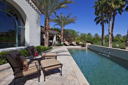 Chaise lounges at poolside in luxury villa