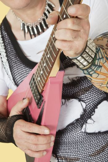 Midsection of senior male punk musician playing guitar