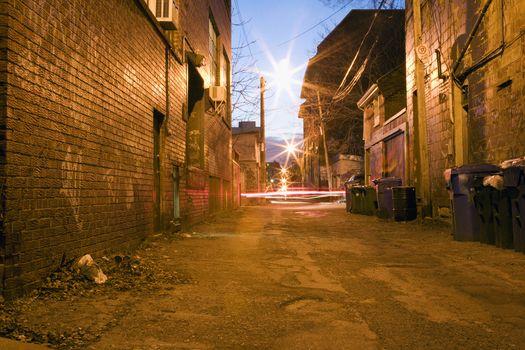 Car head lights in alleyway at dusk