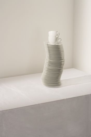 Stack of plates and cups on table elevated view
