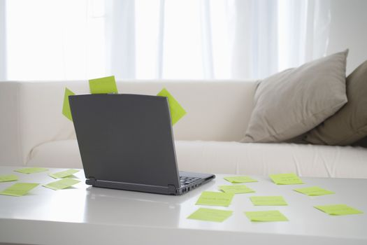 Adhesive notes scattered on table with laptop