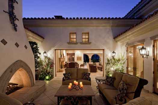 Fireplace with seating furniture in courtyard of luxury mansion in night