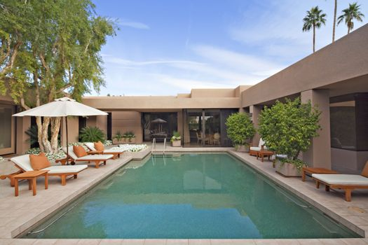 Swimming pool with chaise lounge in luxury villa