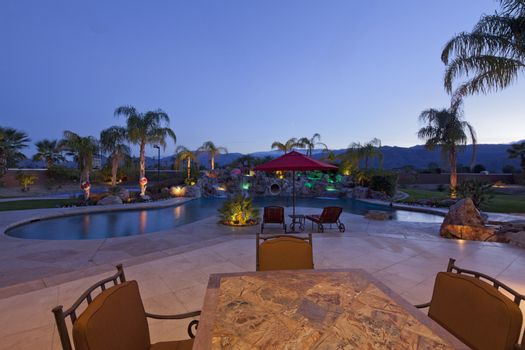 Swimming pool with chaise lounge outside mansion at dusk