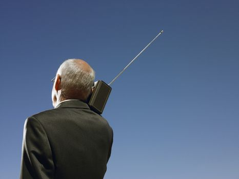 Businessman with radio on shoulder head and shoulders back view