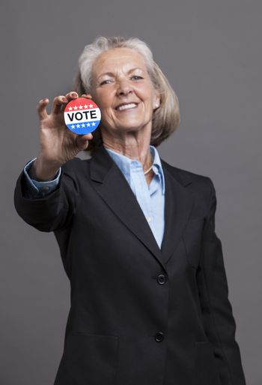 Portrait of senior businesswoman holding voter campaign pin
