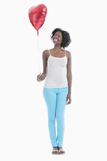 Happy young woman looking at heart shaped balloon over white background