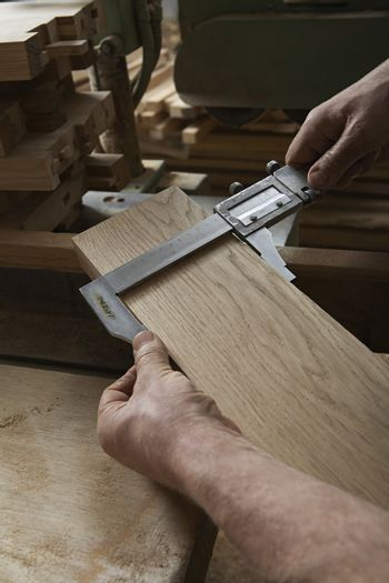 Carpenter Measuring Thickness of Wood Piece