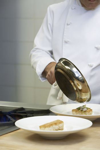 Male chef holding frying pan serving food onto dishes in kitchen