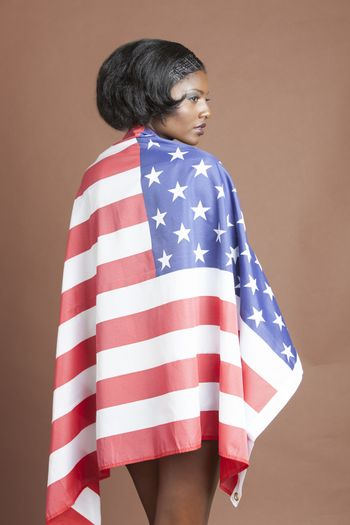 Portrait of african american woman covering herself with american flag