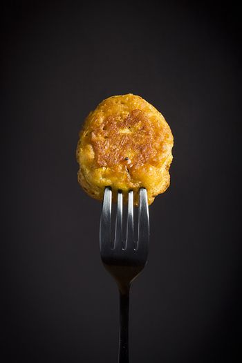 Corn pancakes on a fork on a black background