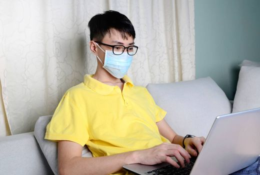 An asian man is working from home during pandemic coronavirus  Covid-19. Ccoronavirus covid 19 infected patient in quarantine room using computer.