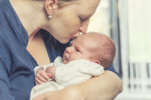 Side view of young mother holding a cute newborn boy in her arms and kissing him on the cheek.