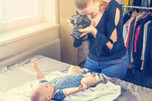 Side top view of mother taking a picture of her baby by DSLR camera. Child is stretching his arms and looks at the camera.