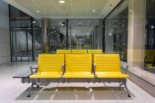 Rows of yellow benches in a waiting area at the airport.