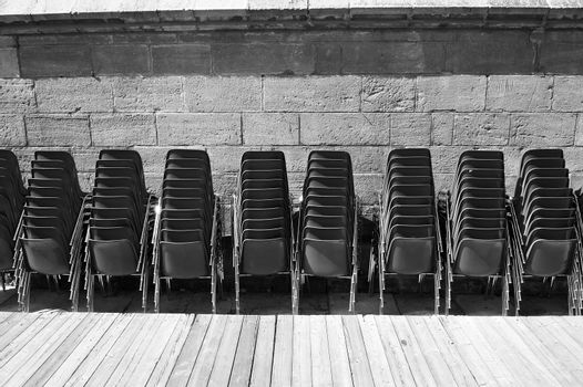Rows of plastic chairs near a concert hall in black and white.  Cultural institutions are closed for quarantine