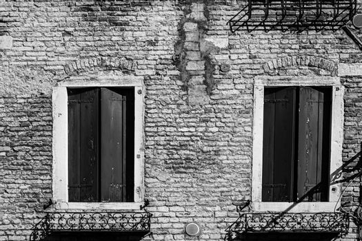 Italian culture on Venetian facades in black and white. Venice is rich and poor, well-groomed and abandoned, reflected in its windows.