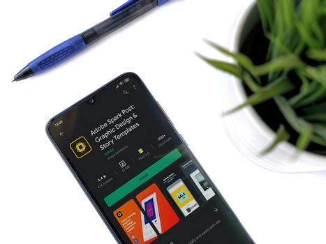 Lod, Israel - July 8, 2020: Modern minimalist office workspace with black mobile smartphone with Adobe Spark Post app play store page on a white background. Close up top view flat lay.