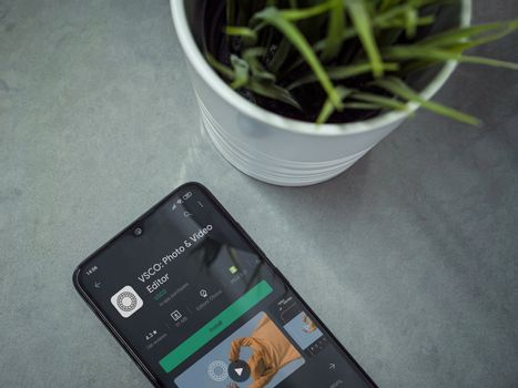 Lod, Israel - July 8, 2020: Modern minimalist office workspace with black mobile smartphone with VSCO - Photo and Video Editor app play store page on a marble background. Close up top view flat lay.