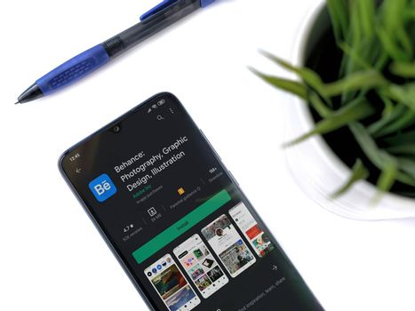 Lod, Israel - July 8, 2020: Modern minimalist office workspace with black mobile smartphone with Adobe Behance app play store page on a white background. Close up top view flat lay.