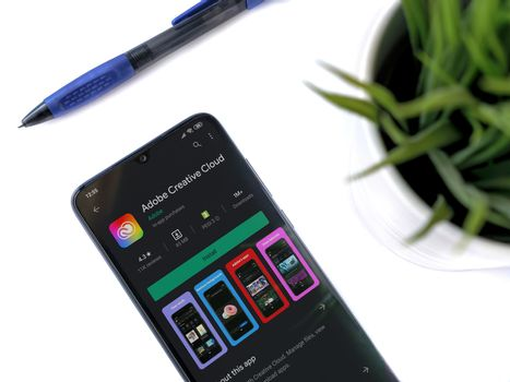Lod, Israel - July 8, 2020: Modern minimalist office workspace with black mobile smartphone with Adobe Creative Cloud app play store page on a white background. Close up top view flat lay.