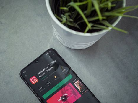 Lod, Israel - July 8, 2020: Modern minimalist office workspace with black mobile smartphone with InShot - Video Editor & Movie Maker app play store page on a marble background.Closeup top view flat lay