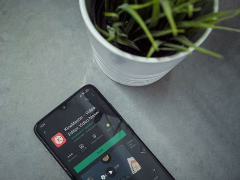 Lod, Israel - July 8, 2020: Modern minimalist office workspace with black mobile smartphone with KineMaster - Video Editor & Movie Maker app play store on marble background. Closeup top view flat lay