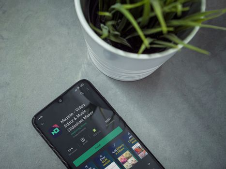 Lod, Israel - July 8, 2020: Modern minimalist office workspace with black mobile smartphone with Magisto - Video Editor & Movie Maker app play store page on marble background.Closeup top view flat lay