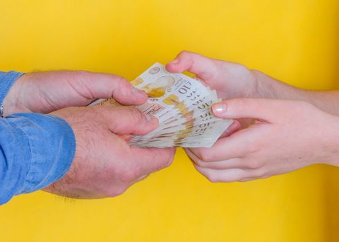 people passing money each other on yellow background