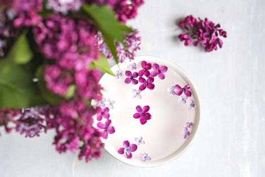 Five-pointed lilac flower among lilac flowers in a cup with water. Lilac branch with a flower with 5 petals.