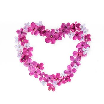 Heart made of lilac petals. Greeting card with heart and five-pointed lilac flower. Copy space
