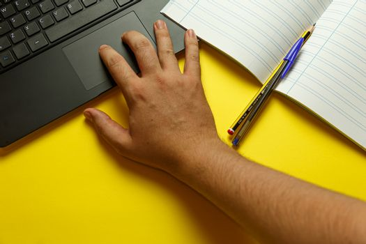 Point of view of a young hand scrolling on the laptop while studying