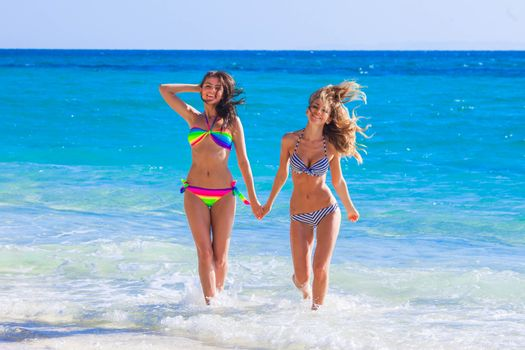Two female friends run from sea waves to beach holding hands and laughing