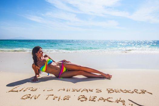 Woman in bikini lies on sea beach , Life is always better on the beach, conceptual handwriting on sand