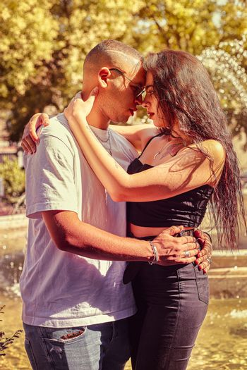 Loving young couple at the park with a fountain at sunset