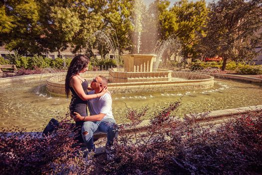 Portrait Young loving couple at the park with a fountain at sunset