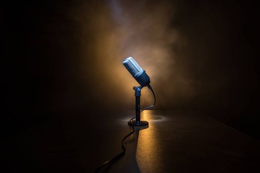 Microphone for sound, music, karaoke in audio studio or stage. Mic technology. Speech broadcast equipment. Microphone in dark room on table with backlight. Selective focus