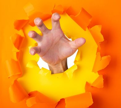 man hand with anger feeling through a hole in orange paper