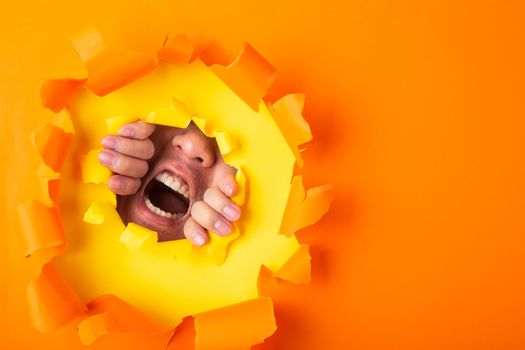 man screaming out from behind hole of orange paper
