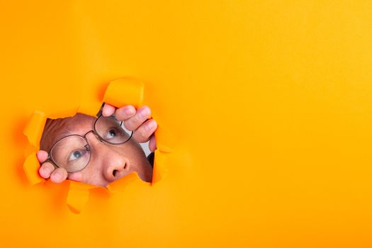 The man with spectacle peeks through a cut hole
