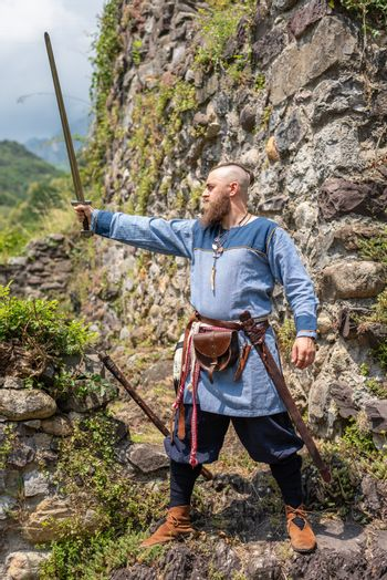 Medieval warrior brandishes his sword raising it to the sky, Viking in traditional clothes