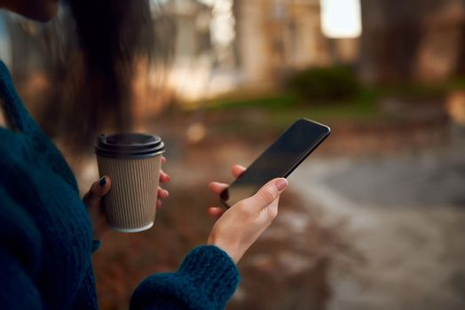 Cropped shot of young woman hands with a smartphone and disposable cup of hot drink on defocused urban background
