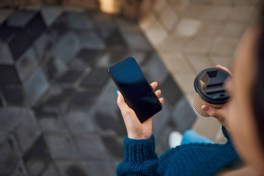 Top view of young lady holding smartphone and paper cup while walking in the city